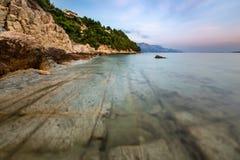多岩石的海滩和透明亚得里亚海在Omis附近 库存照片