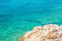 多岩石的海滩和水晶蓝色海 图库摄影