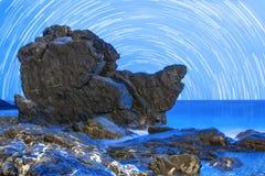 多岩石的海滩在蓝色小时内 免版税库存照片