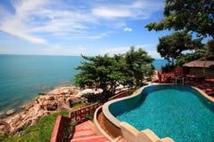 多平实海视图游泳池、太阳懒人在庭院旁边和大厦 免版税库存图片