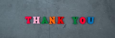 多彩多姿感谢您词由木信件做成在灰色涂灰泥的墙壁背景 库存照片