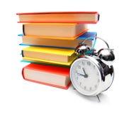 多彩多姿的书和闹钟。 库存图片