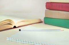 多彩多姿的书,加起和一本开放书,在笔记本旁边 教育、知识和自我发展的概念 免版税库存照片
