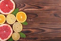 多彩多姿的切片水多的橙色,成熟柠檬和新鲜的葡萄柚与鲜绿色的叶子在一张黑褐色木桌上 免版税库存图片
