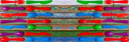 多彩多姿的塑料匙子、叉子和刀子在老木色的背景 库存图片