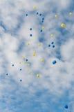 多彩多姿的气球在与云彩的清楚的蓝天飞行 库存照片