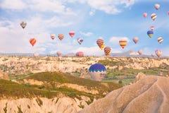 多彩多姿的气球飞行在岩石 免版税库存照片