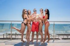 多彩多姿的游泳衣的愉快的朋友喝鸡尾酒的在旅馆在海滩附近 夏天海滩党 22个项目符号口径组白色 免版税库存图片