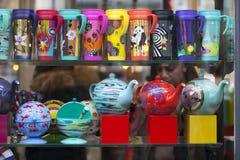 多彩多姿的热水瓶、杯子和盘子在商店窗口里 免版税库存图片