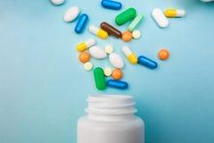 多彩多姿的片剂和胶囊,片剂的,在蓝色背景,再镇痛药的配药医学药片白色瓶 图库摄影