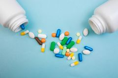 多彩多姿的片剂和胶囊,片剂的,在蓝色背景,再镇痛药的配药医学药片白色瓶 免版税库存照片