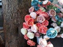 多彩多姿的综合性花外面在树干附近的街道上 免版税库存照片
