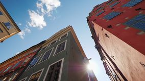 多彩多姿的老房子在斯德哥尔摩 美好的欧洲建筑学,太阳发光从房子的屋顶的后面 免版税库存图片