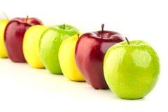 多彩多姿的苹果连续在一张白色桌上 免版税库存照片