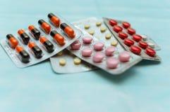 多彩多姿的药片和胶囊在水泡特写镜头,在蓝色背景 对待人的疾病的概念 免版税图库摄影