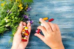多彩多姿的药片,胶囊在手中在蓝色背景 免版税库存图片