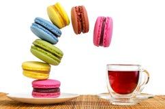 多彩多姿的蛋糕makaroons落往杯子红色茶 免版税图库摄影