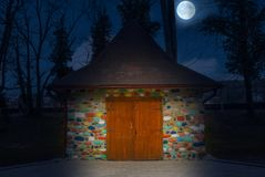 多彩多姿的被绘的小的房子在与满月的晚上 象童话当中的五颜六色的石房子 库存图片