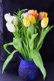 多彩多姿的郁金香花束在一个蓝色花瓶的在一块灰色布料 下雨 言情 免版税库存图片