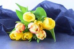 多彩多姿的郁金香花束在一块灰色布料的 下雨 言情 免版税库存照片