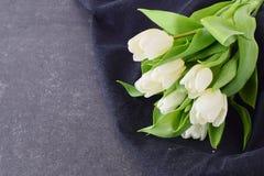 多彩多姿的郁金香花束在一块灰色布料的 下雨 言情 免版税库存图片