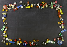 多彩多姿的玻璃大理石球和玻璃小卵石在黑surfa 库存照片