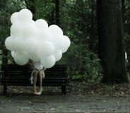 多愁善感。乡情。有气球的孤独的妇女坐长凳在公园 库存照片