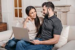 多文化夫妇在家坐沙发有在膝盖的膝上型计算机的 免版税库存照片