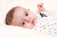 多斑点的上面的美丽的女婴在奶油色毛皮地毯 免版税图库摄影