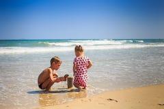 多斑点的男孩戏剧的小女孩在海滩波浪海浪边缘  免版税库存照片