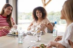 多族群三名愉快的年轻妇女吃和谈话在晚餐会期间 库存照片
