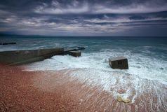 多暴风雨的天气和一个混凝土结构海岸线障碍与以远海 免版税库存照片