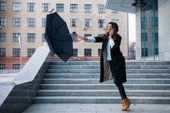 多暴风雨的天气 黑女孩抓住飞行伞 库存图片
