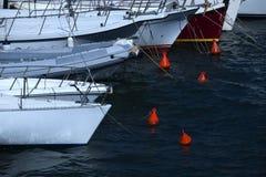 多条小船栓了到浮体在海湾 免版税库存图片