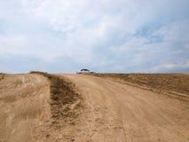 多灰尘的土路带来了小山的汽车 免版税库存图片