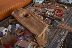 多灰尘的木匠` s书桌和工具,打火机,剪刀,沙纸,笔 图库摄影
