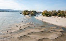 多瑙河的低潮有走在沙子海岛上的人剪影的在水撤退在诺维萨德,塞尔维亚人以后 库存图片