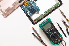 多用电表和残破的片剂,电子在维修车间 免版税库存照片