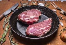 水多的新鲜的未加工的有一把刀子的猪肉牛排老生铁平底锅肉叉子草本和香料大蒜木土气背景的c 库存图片