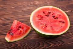 水多的有机西瓜特写镜头在木背景的 西瓜黏浆状物质是甜的,并且外皮是绿色的 美满的果子石榴红色种子夏天 库存照片