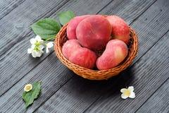 水多的桃子和花在篮子 库存照片