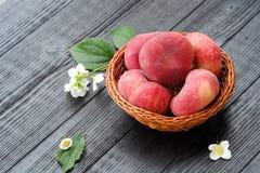 水多的桃子和花在篮子 免版税库存图片
