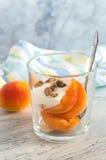 水多的桃子用李子和坚果在一块玻璃在一张桌上与一块镶边餐巾 免版税图库摄影