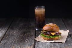 水多的汉堡用在木背景的冷的可乐 免版税库存图片