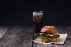 水多的汉堡用在木背景的冷的可乐 图库摄影