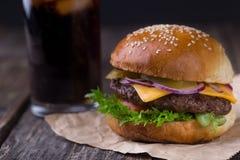 水多的汉堡用在木背景的冷的可乐 库存图片