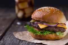 水多的汉堡用在木背景的冷的可乐 免版税库存照片