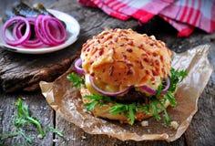 水多的汉堡用牛肉、乳酪、莴苣、酸黄瓜、烂醉如泥的葱和乳酪大面包 库存图片