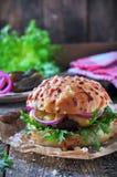 水多的汉堡用牛肉、乳酪、莴苣、酸黄瓜、烂醉如泥的葱和乳酪大面包 图库摄影