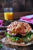 水多的汉堡用牛肉、乳酪、莴苣、酸黄瓜、烂醉如泥的葱和乳酪大面包 免版税库存图片